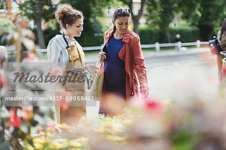 Female florist helping pregnant shopper at flower shop storefront