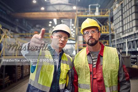 Steelworkers talking, gesturing in steel mill