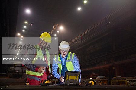 Steelworkers using laptop in dark steel mill
