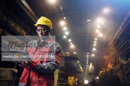 Steelworker using digital tablet in steel mill