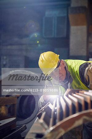 Focused steelworker with flashlight examining steel part in steel mill
