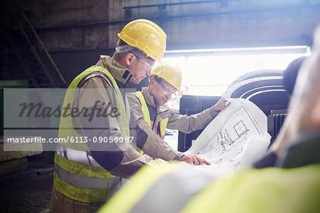 Engineer and steelworker examining blueprints in steel mill