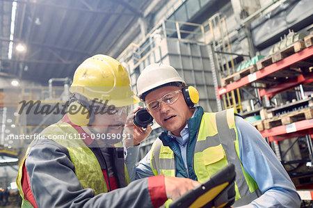 Steelworkers wearing ear protectors using digital tablet in steel mill