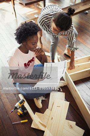 Women assembling furniture, reading instructions