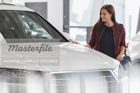 Female customer shopping for new car in car dealership showroom