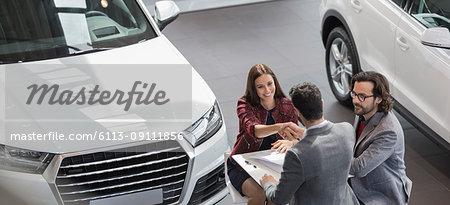 Car salesman shaking hands with female customer in car dealership showroom