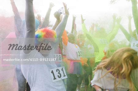 Playful charity run runners throwing holi powder