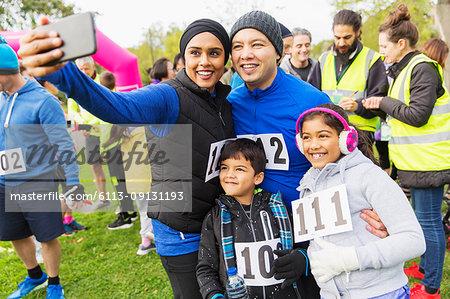 Family charity run runners taking selfie with camera phone