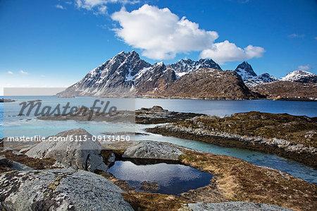 Craggy mountains below blue winter sky above fjord, Sund, Flakstadoya, Lofoten, Norway