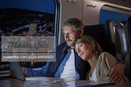 Affectionate wife sleeping on husband using laptop on passenger train at night