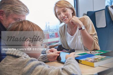 Family using smart phone on passenger train