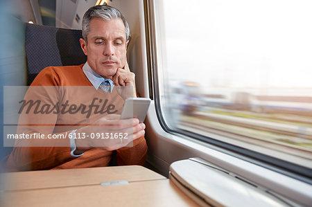Focused businessman using smart phone at passenger train window