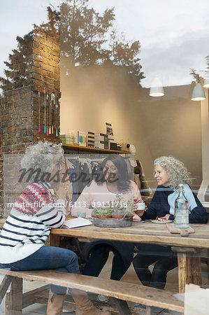Women friends drinking tea in cafe shop window