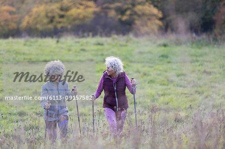 Active senior women friends hiking with poles up rural hillside