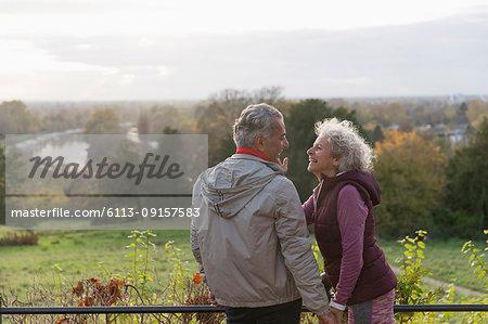 Smiling, affectionate active senior couple in autumn park