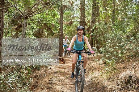 Carefree woman mountain biking on trail in woods