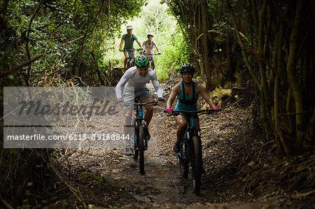Friends mountain biking on trail in woods