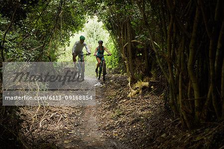 Couple mountain biking on trail in woods