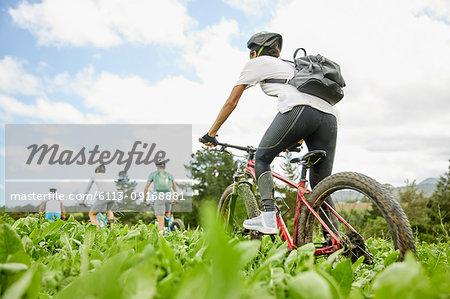 Friends mountain biking in rural field