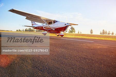 Prop airplane landing on sunny tarmac