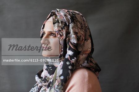 Serene, thoughtful woman wearing floral hijab, looking away