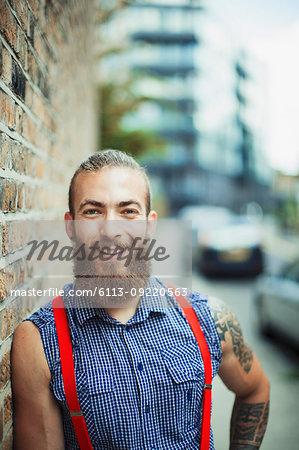 Portrait confident, smiling male hipster on urban sidewalk