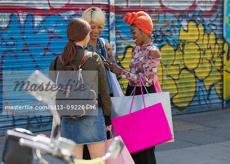 Young women friends shopping, talking on urban sidewalk