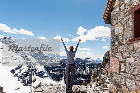 Exuberant female hiker on sunny, snowy mountaintop, Yoho Park, British Columbia, Canada