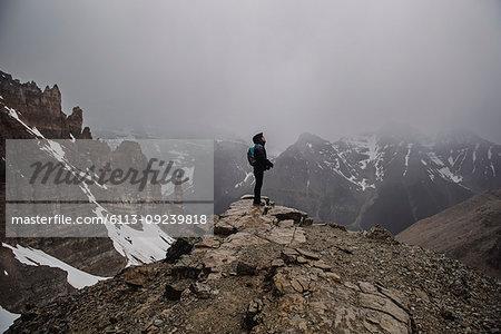 Female hiker on top of craggy, foggy mountain Banff, Alberta, Canada