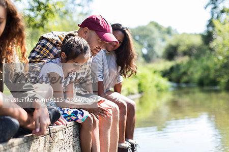 Family sitting at the edge of riverside dock