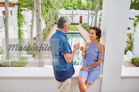Mature couple drinking mimosas on hotel balcony