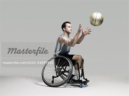Wheelchair basketball player catching ball