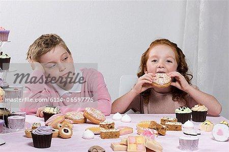 Boy looking at girl eating doughnut