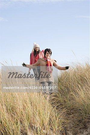 Female friends walking in marram grass