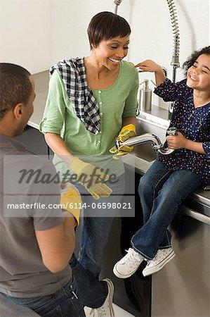 Family doing plumbing in kitchen