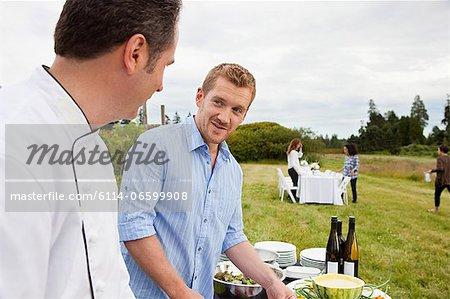 Men preparing meal in a field
