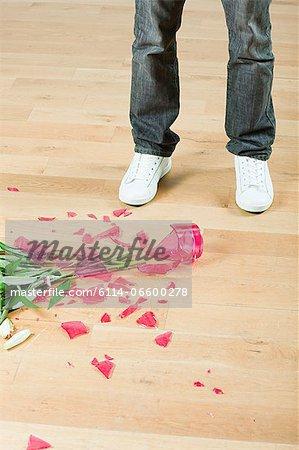 Young man with broken vase of flowers on floor