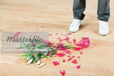Young Man With Broken Vase Of Flowers On Floor Stock Photo