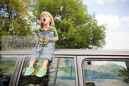 Boy with binoculars, sitting on roof of car