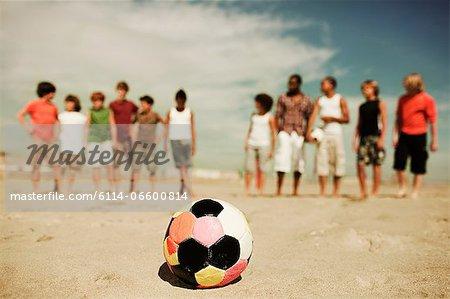 Boys standing on beach with football