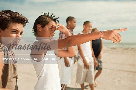 Boys on beach, one boy pointing