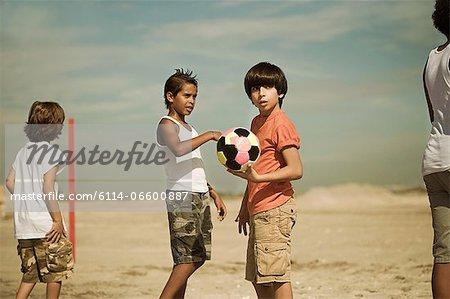 Boys on beach with football
