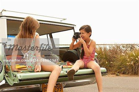 Two girls sitting in estate car taking photograph