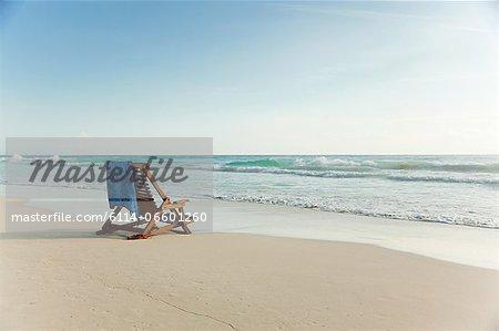 Deck chair on sandy beach at water's edge