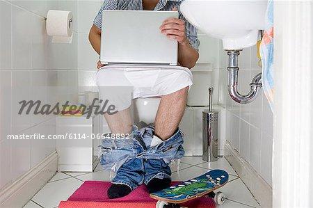 Man on toilet using laptop