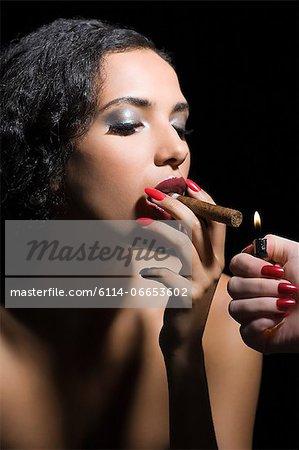 Woman lighting a cigar