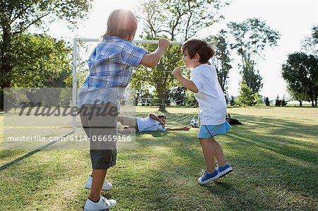 Boys scoring goal against dad