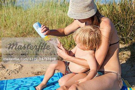 Croatia, Dalmatia, Mother Applying Sun Cream On Her Sons Hand