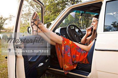 Croatia, Dalmatia, Young woman sits in car applying lipstick