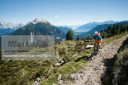 Mountain biker riding on Alpine trail, Tyrol, Austria